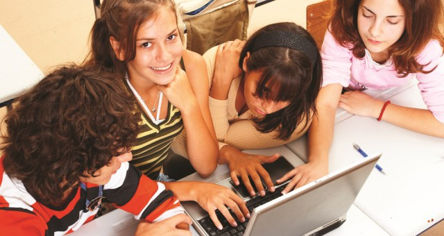 Four girls learn fast on computer together.