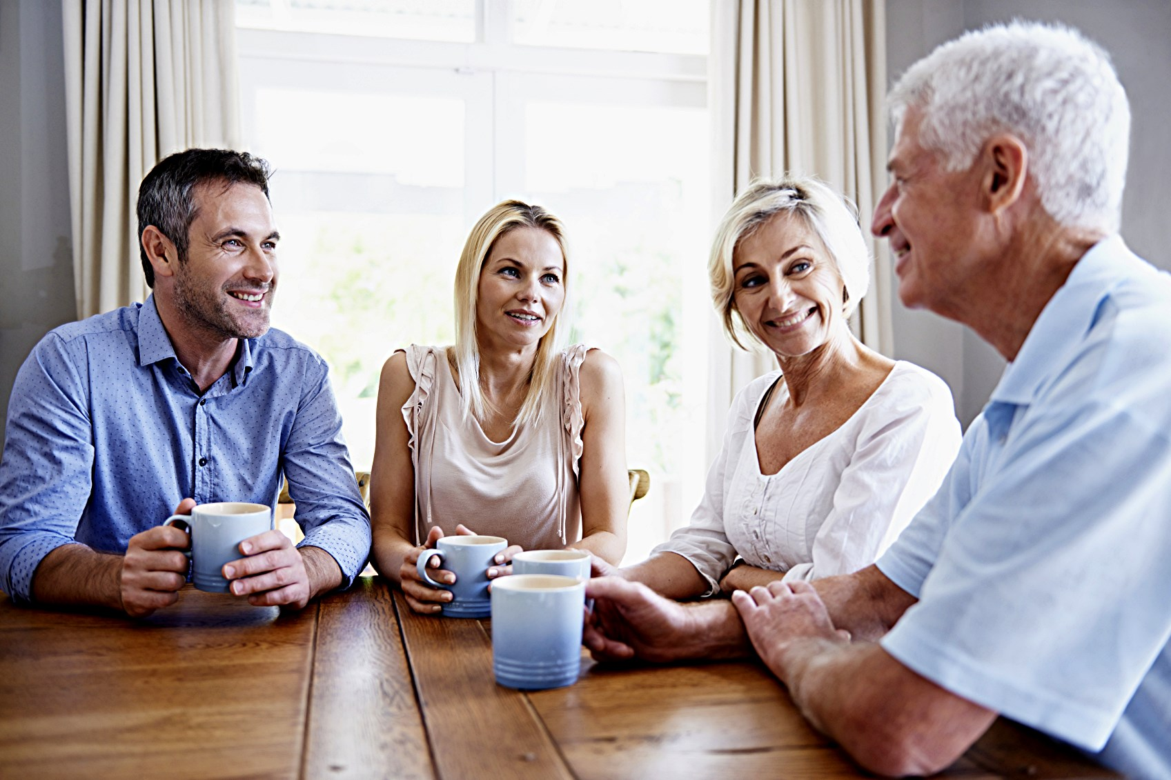 An older couple and a younger couple drinking coffee at the table, smiling because the older man has learned to tell better stories